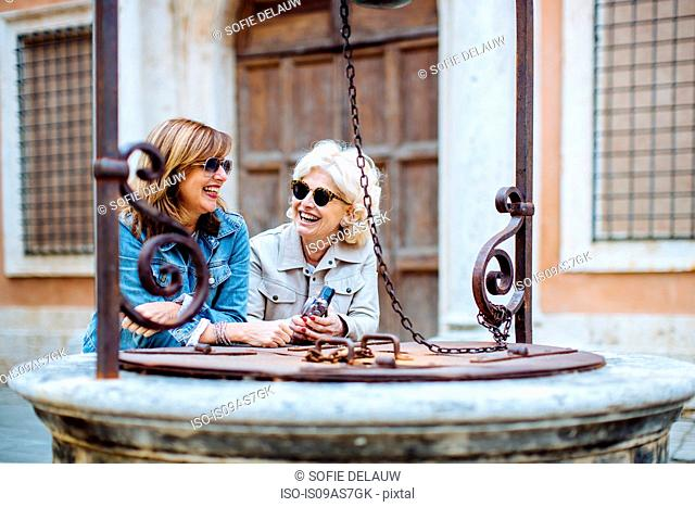 Two mature female friends chatting at water well, Tuscany, Italy