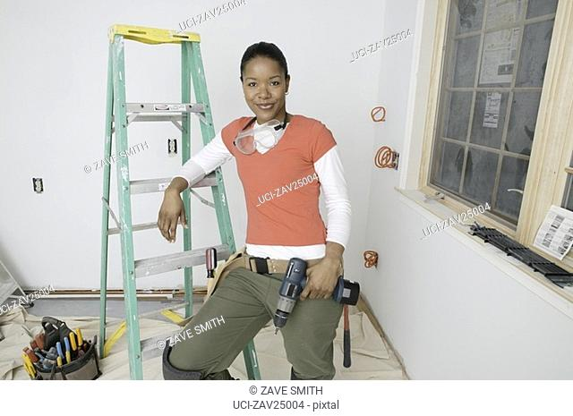 African woman holding power drill