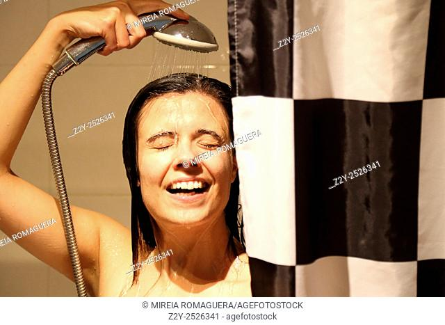 Smily young woman with eyes closed showering