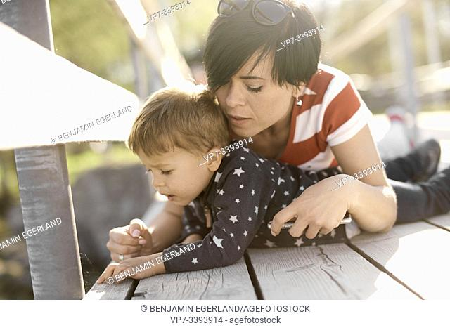 caring mother laying with son on floor outdoors, exploring