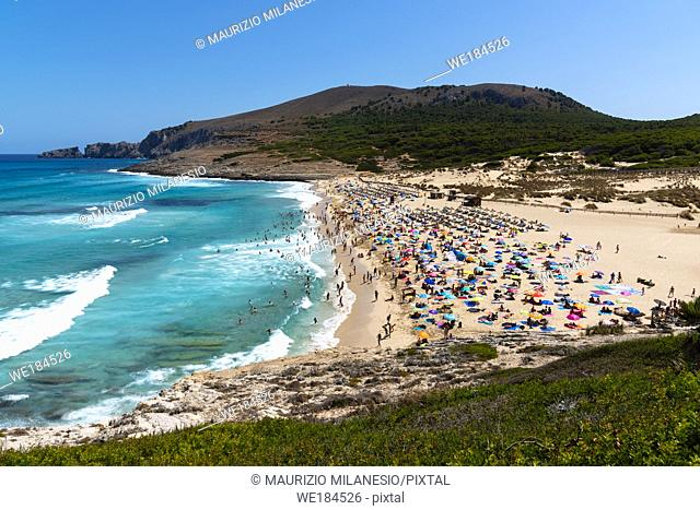 view on the beach of Cala Mesquida Majorca Spain with many tourists and rough sea
