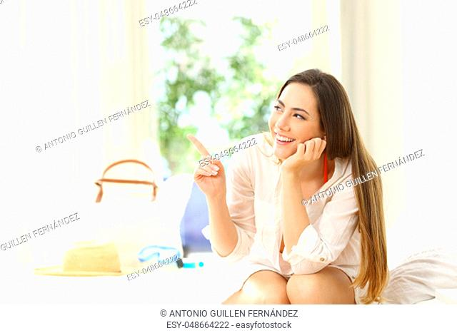 Hotel guest pointing at side sitting on a bed on summer holidays
