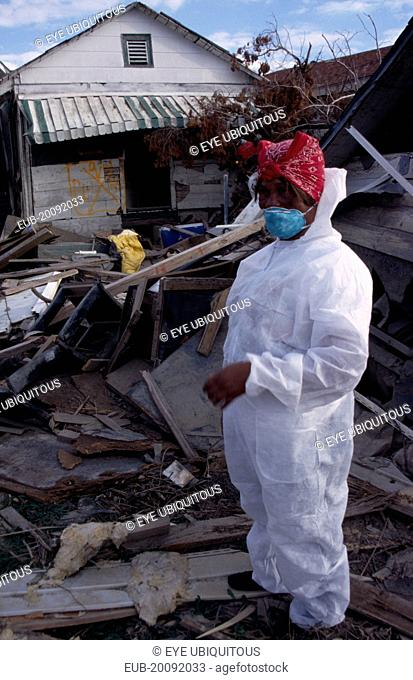Aftermath of 2005 Hurricane Katrina, woman wearing protective clothing standing amongst wood and other debris from destroyed buildings