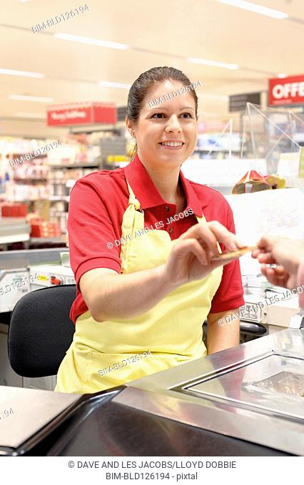 Hispanic worker returning credit card to customer at checkout