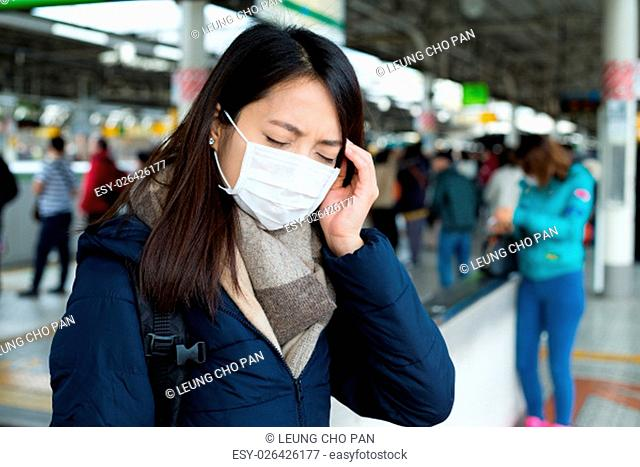 Woman suffer from headache and standing at train station