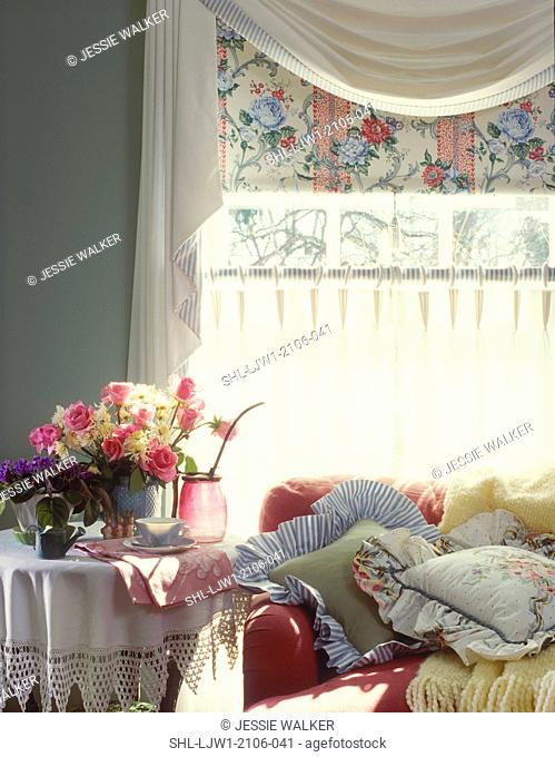 FAMILY ROOMS- Detail of round end table covered with antique crocheted and linen tablecloth, flowers, rasberry colored sofa covered with pillows, yellow throw