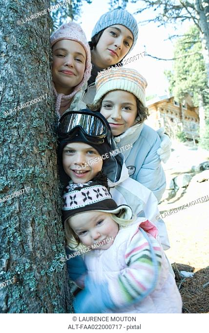 Group of teens and children dressed in winter clothes, posing next to tree, portrait