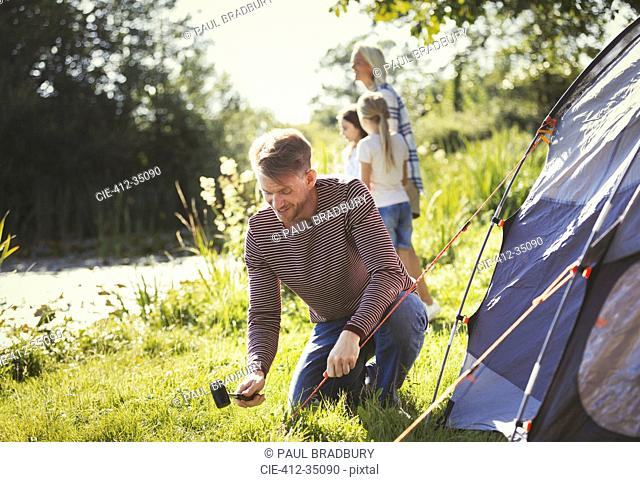 Father pitching tent at sunny lakeside campsite