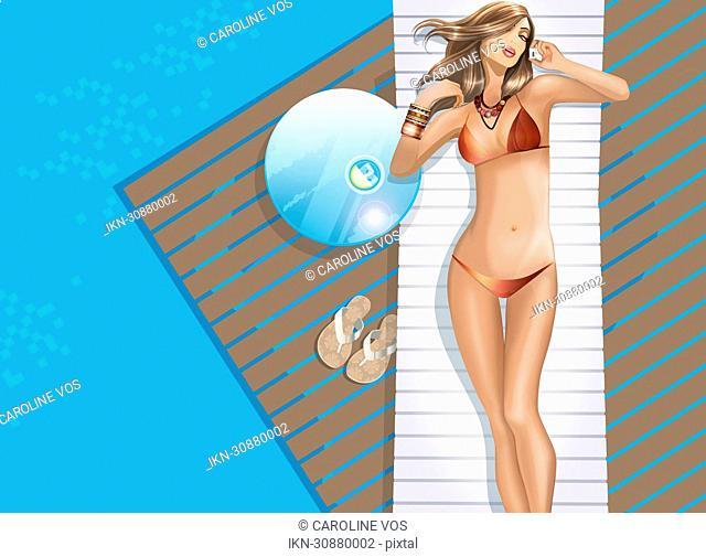 Sexy woman in bikini talking on cell phone at poolside