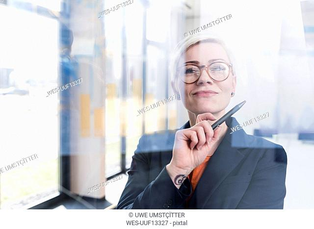 Portrait of confident businesswoman behind glass pane in office