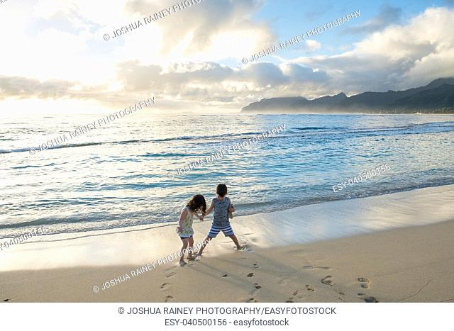 Siblings experiencing the beach and ocean together while on a tropical vacation to Oahu Hawaii with nice warm weather even at sunrise