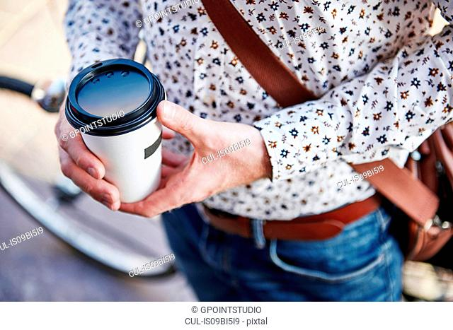 Man holding drink in disposable cup, cropped