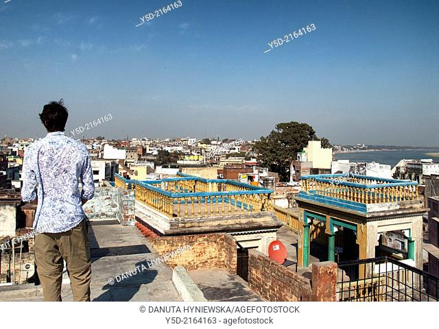 young man watching distant urban landscape of Varanasi city from the roof, Benares, Banaras, Uttar Pradesh, India, Asia