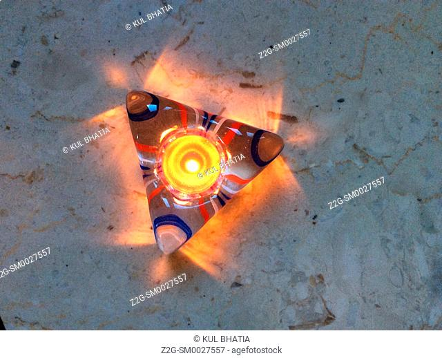 A small candle in a triangular ashtray casts warm, colorful glow on a marble base, Montreal, Canada
