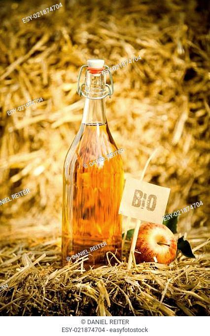 A bottle of natural apple cider vinegar on straw