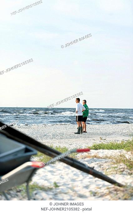 Men standing on beach and looking at sea