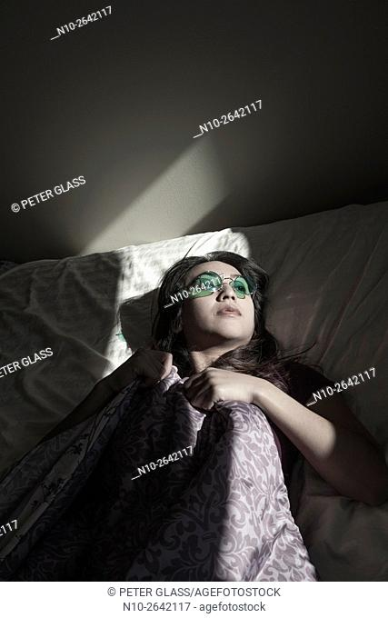 Young Asian woman lying on her bed, wearing colored glasses