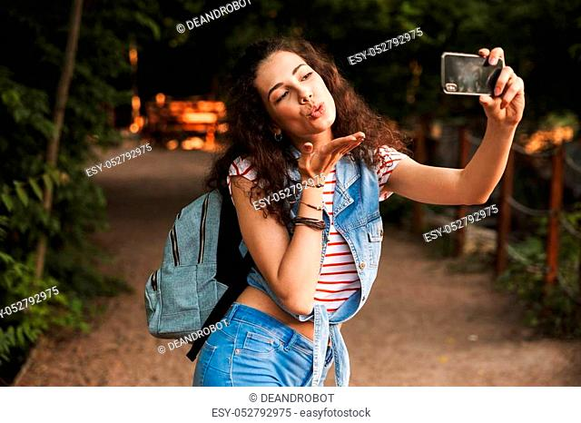 Photo of beautiful teenage woman 18-20 with backpack blowing air kiss on mobile phone camera and taking selfie while walking outdoor