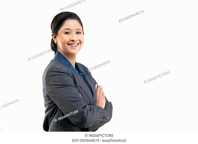 Portrait of young happy businesswoman in suit isolated over gray background