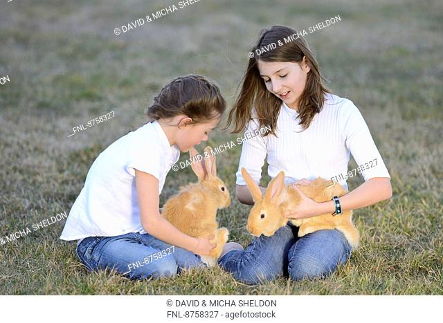 Two children with her rabbits on a meadow, Upper Palatinate, Bavaria, Germany, Europe
