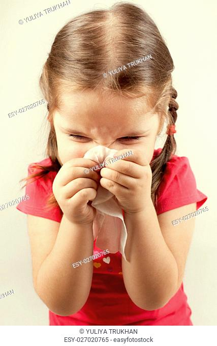 Little girl wipes her nose with a tissue
