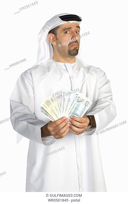 Mid adult man holding paper currency, portrait