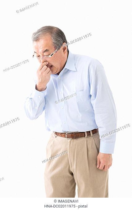 Senior man holding nose