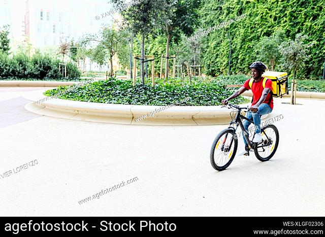 Young delivery man wearing helmet cycling on footpath