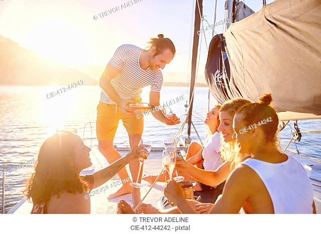 Friends drinking champagne on sunny catamaran