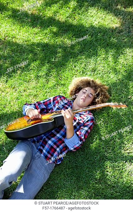 Teenage boy playing his guitar on the grass