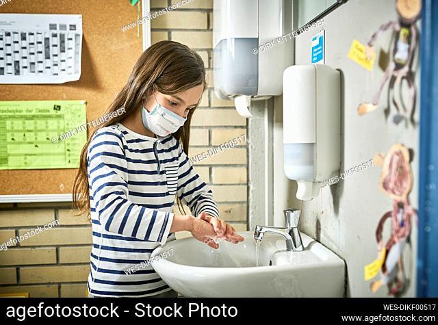 Girl wearing mask in school washing her hands