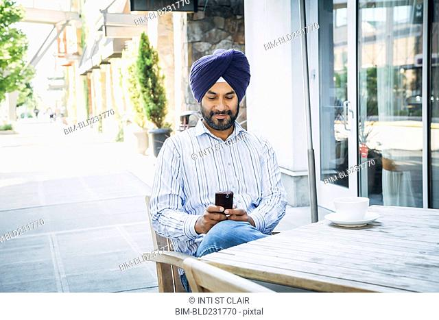 Man wearing turban texting on cell phone at cafe