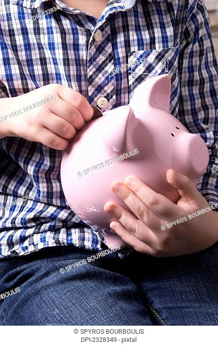 Young Boy Depositing Coins Into A Piggy Bank; Laval, Quebec, Canada