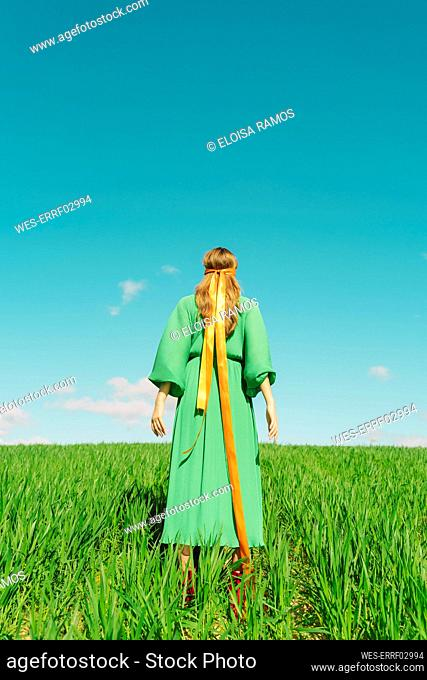 Rear view of young woman wearing a green dress standing in a field with a ribbon around her head