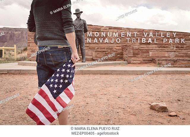 USA, Utah, man with american flag at Monument Valley entry