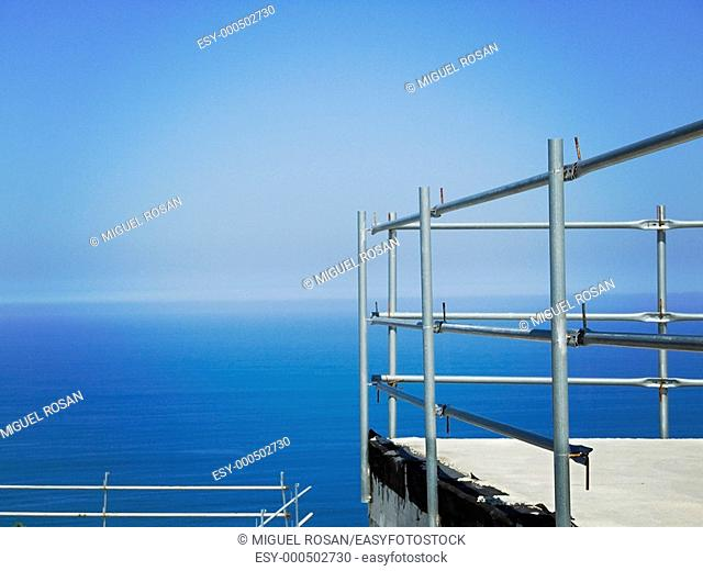Terrace under construction along the Mediterranean Sea on the Costa Brava with scaffolding and metal protection