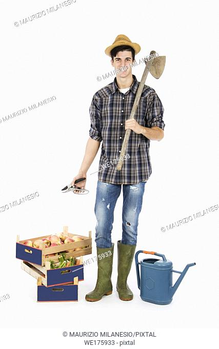 Young farmer with shears in his hand and hoe on his shoulder, at his feet crates with fruit and vegetables, he is wearing a straw hat
