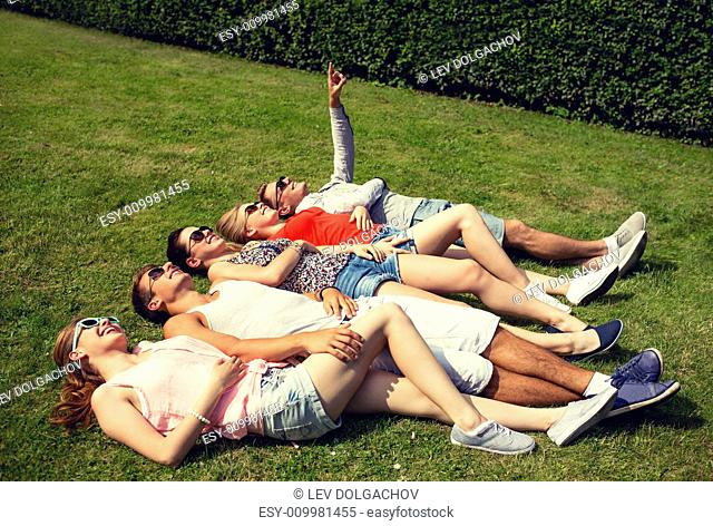 friendship, leisure, summer and people concept - group of smiling friends lying on grass outdoors