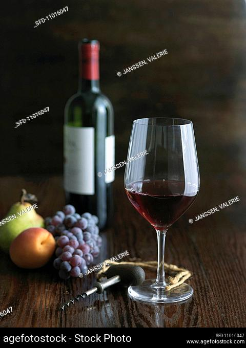 Single Glass of Red Wine with Fruit, Corkscrew and Wine Bottle