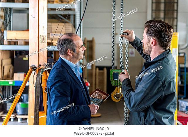 Manager and worker in workshop, hoist