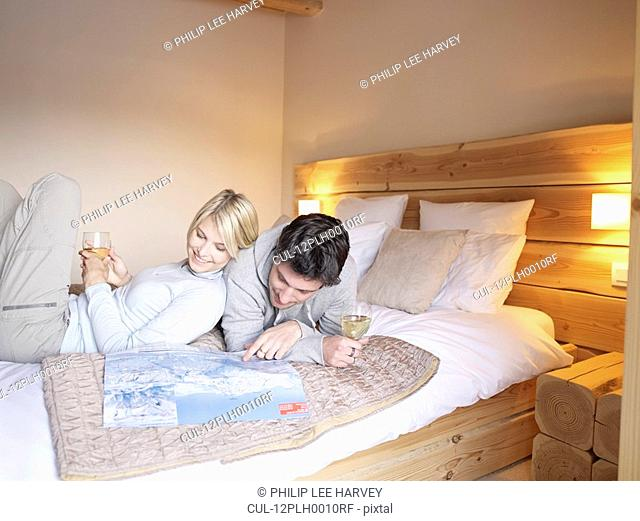 woman and man lying on reading map