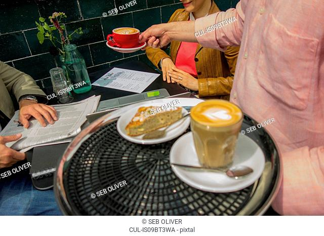 Waiter with tray of food and drinks, London, UK