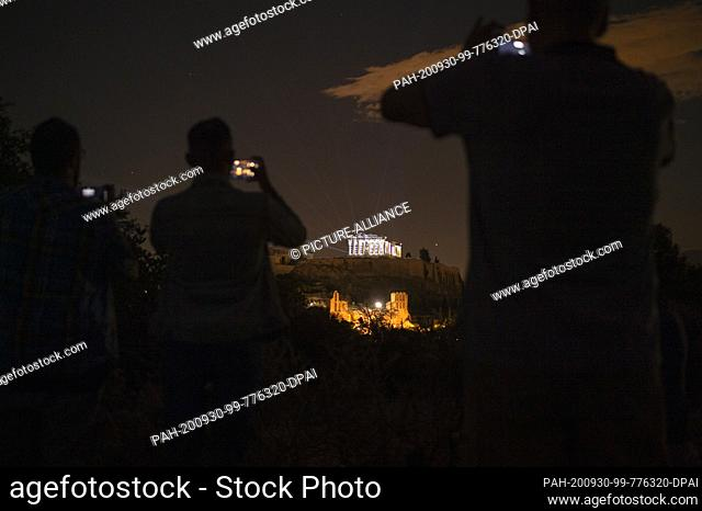 30 September 2020, Greece, Athen: People film and photograph the Acropolis with their mobile phones as it appears in a new light: a new lighting system was...