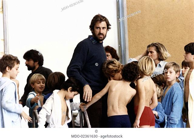 Italian actor Nanni Moretti surrounded by some kids at the swimming pool in Red Lob. 1989