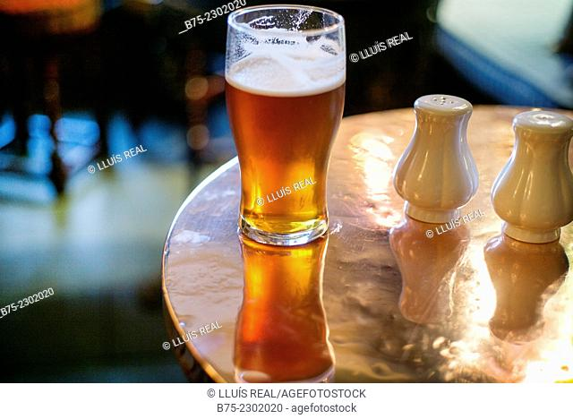 Closeup of a glass of a pint of ale and shakers on a table in a pub in Yorkshire, England, UK