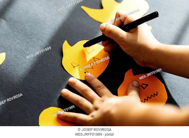 Little boy's hand painting faces on cardboard pumpkins for Halloween