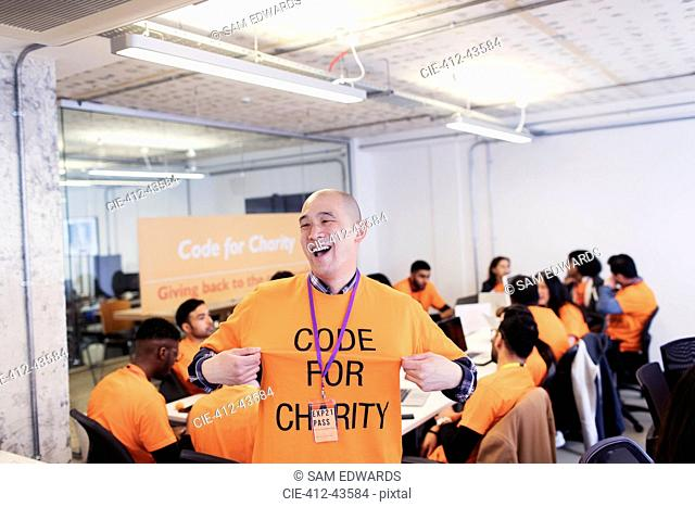 Playful hacker with t-shirt coding for charity at hackathon