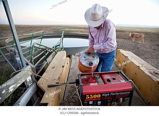 Yoder, Colorado - Dick Tanner fills a generator with red-dyed diesel fuel to pump water for cattle on the Bohart Ranch  Windmills normally do the job