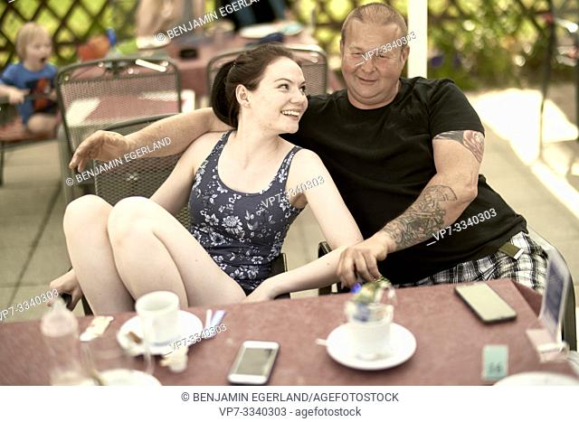middle-aged father with young adult daughter sitting together at table in outdoor café