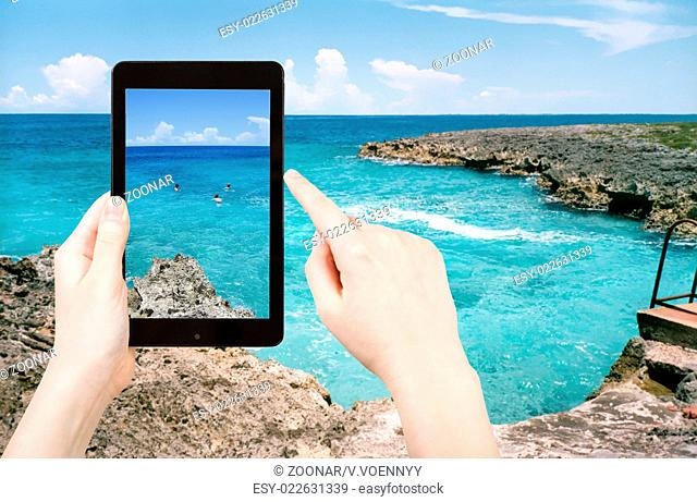 tourist taking photo of stone coastline of Caribbean Sea